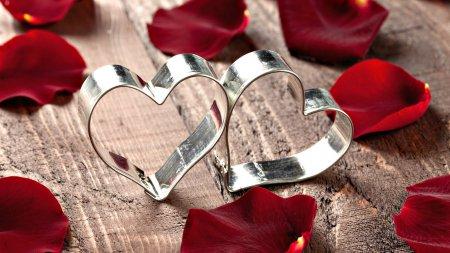 Сердце из роз кораллового цвета, украшенное атласной лентой, - повод для выражения глубины чувств.